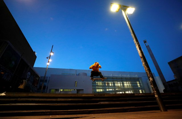 """Bulgarian skateboarder Petar """"Stewie"""" Stantchev, 25, does a trick, known as a frontside ollie, in front of Barcelona Contemporary Art Museum (MACBA) in Barcelona, Spain on November 11, 2020. (Photo by Nacho Doce/Reuters)"""