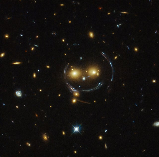 "The galaxy cluster SDSS J1038+4849 is pictured in this undated handout image taken with the NASA/ESA Hubble Space Telescope. As a result of the phenomenon of gravitational lensing, it seems to be smiling. In the case of this ""happy face"", the two eyes are very bright galaxies and the smile lines are actually arcs caused by strong gravitational lensing. 