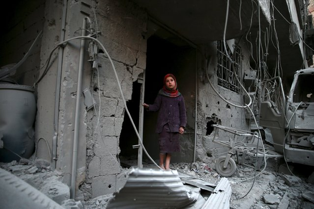 A girl inspects damage in a site hit by what activists said were airstrikes carried out by the Russian air force in the town of Douma, eastern Ghouta in Damascus, Syria January 10, 2016. (Photo by Bassam Khabieh/Reuters)