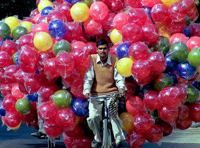 An Indian man carries plastic balls on his bicycle in the northern Indian city Lucknow February 16, 2006. (Photo by Pawan Kumar/Reuters)