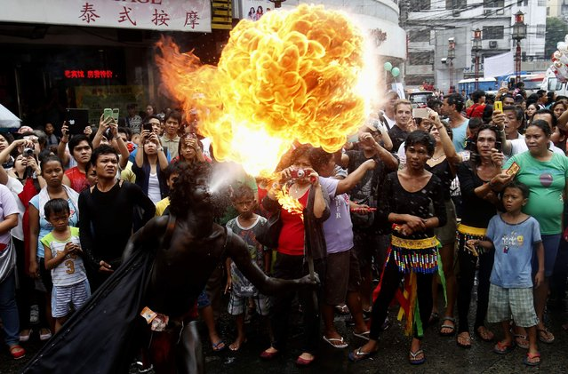 A reveller blows fire to celebrate Lunar New Year at Manila's Chinatown February 19, 2015. (Photo by Erik De Castro/Reuters)
