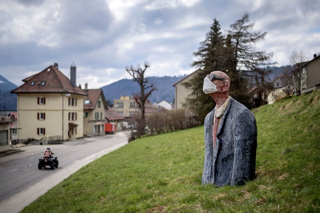 A picture taken on April 18, 2020 in Sainte-Croix shows a scultpure representing a man wearing a facemask as a preventive measure against the Covid-19 coronavirus in a field. (Photo by Fabrice Coffrini/AFP Photo)