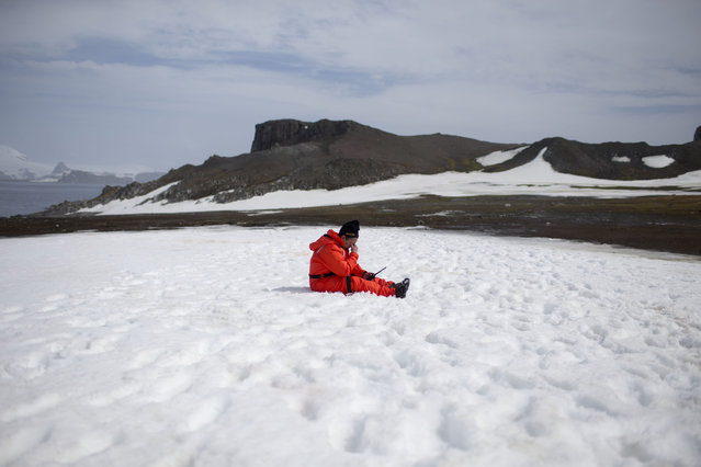 In this January 24, 2015 photo, a worker from the Chile's Antarctic Institute sits on the snow on Robert Island, part of the South Shetland Islands archipelago in Antarctica. NASA uses the remoteness of Antarctic to study what people would have to go through if they visited Mars. The dry air also makes it perfect for astronomers to peer deep into space and into the past. (Photo by Natacha Pisarenko/AP Photo)