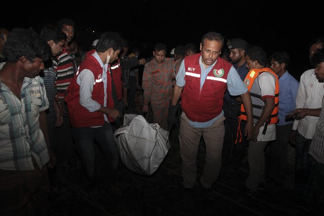 Bangladeshi rescue workers carry the dead body of one of the victims after a river ferry carrying unto 140 passengers capsized Sunday after being hit by a cargo vessel,in Manikganj district, about 40 kilometers (25 miles) northwest of Dhaka, Bangladesh, Sunday, February 22, 2015. (Photo by A. M. Ahad/AP Photo)