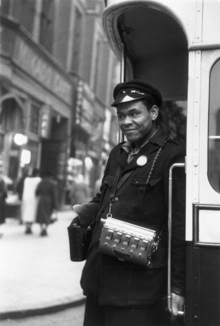 West Indian bus conductor Chandler McGhie makes sure that all his passengers are safely on board before pressing his bell, February 1955. (Photo by Thurston Hopkins/Picture Post/Getty Images)