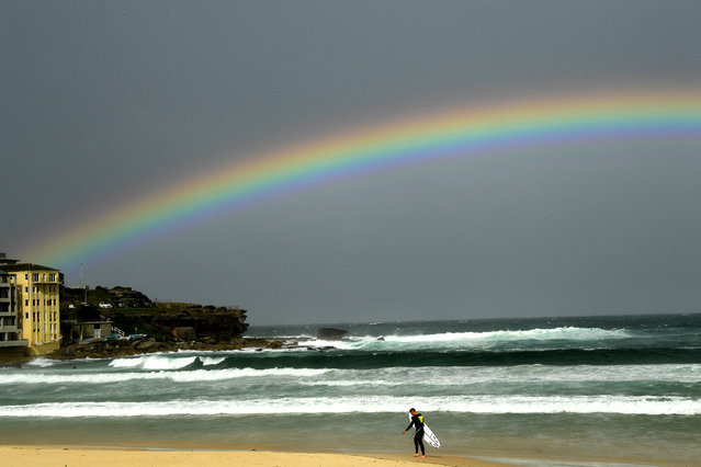 A rainbow is seen as it rains over the Bondi Beach in Sydney on May 6, 2021. (Photo by Saeed Khan/AFP Photo)