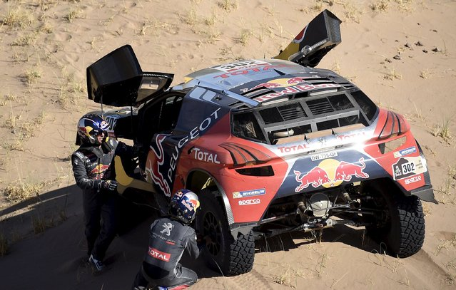 Stephane Peterhansel (L) of France and co-pilot Jean Paul Cottret change a tyre of their Peugeot during the ninth stage of the Dakar Rally 2016 near Belen, Argentina, January 12, 2016. (Photo by Franck Fife/Reuters)