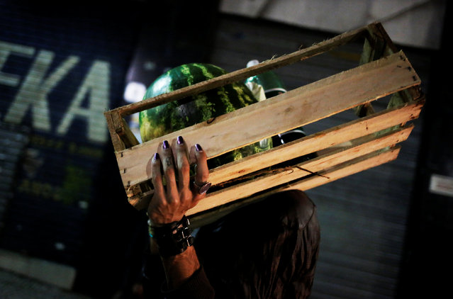 Rodrigo, 26, who is among members of lesbian, gay, bisexual and transgender (LGBT) community, that have been invited to live in a building that the roofless movement has occupied, carries a box of fruit after collecting donations of fruit and lettuce from the municipal market, in downtown Sao Paulo, Brazil, November 11, 2016. (Photo by Nacho Doce/Reuters)