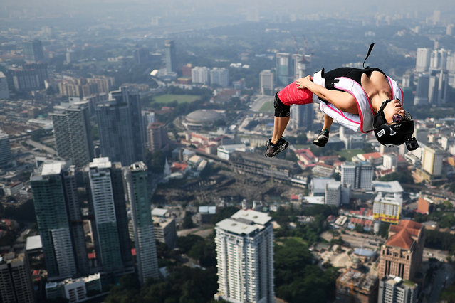 Base jumpers leap from the 300-metre high skydeck of Malaysia's landmark Kuala Lumpur Tower against the backdrop of the city's skyline in Kuala Lumpur on September 30, 2018 during the annual International KL Tower Base-Jump event. (Photo by Manan Vatsyayana/AFP Photo)