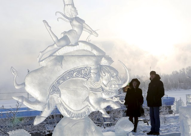 """A couple look at an ice sculpture called """"The Phantom Water"""", created by participants from Moscow, Daria and Vladimir Likhodeyev, on the last day of the annual international festival of snow and ice sculptures """"The Magical Ice of Siberia"""", with the air temperature at about minus 28 degrees Celsius (minus 18.4 degrees Fahrenheit), in Krasnoyarsk, Russia, January 17, 2016. (Photo by Ilya Naymushin/Reuters)"""
