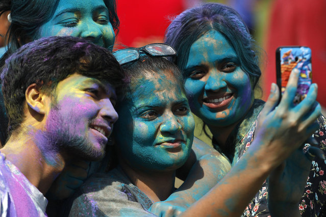 Indians, their faces smeared with colored powder, take a selfie as they celebrate Holi, the Hindu festival of colors, in Ahmadabad, India, Friday, March 6, 2015. Holi, India's joyful and colorful celebration of the arrival of spring along with several religious myths and legends, has long ago ceased to be only a Hindu festival. The streets and lanes across most of India turn into a large playground where people off all faiths throw colored powder and water at each other.(AP Photo/Ajit Solanki)