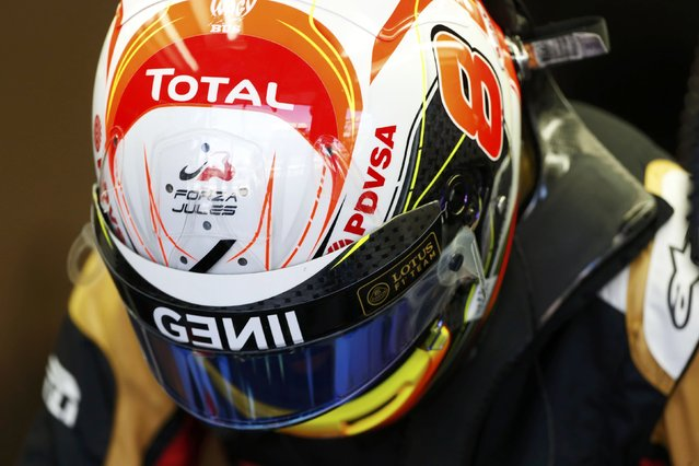 """Lotus Formula One driver Romain Grosjean of France looks down in his garage during the first practice session of the Australian F1 Grand Prix at the Albert Park circuit in Melbourne March 13, 2015. The words """"Forza Jules"""" is in tribute to compatriot and fellow F1 driver Jules Bianchi who is in an induced coma following a crash during the 2014 Japanese Grand Prix. The black diagonal stripe below it is in tribute to the French victims of a helicopter crash in Argentina on Monday.  REUTERS/Brandon Malone"""