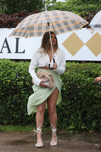 Racegoers shelter from the rain under umbrellas as they pose for photographers on the first day of the Epsom Derby Festival horse racing event in Surrey, southern England on June 4, 2021. (Photo by i-Images Picture Agency)