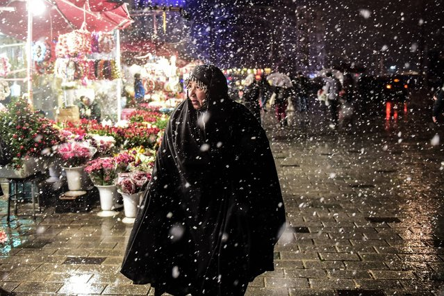 A woman walks under the snow at Taksim Square in Istanbul on December 16, 2016. (Photo by Yasin Akgul/AFP Photo)
