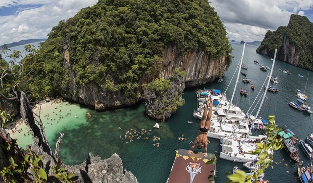 In this handout image provided by Red Bull, Artem Silchenko of Russia prepares to launch an armstand dive from the 27 metre platform on Hong Island in the Andaman Sea during the last competition day of the eighth and final stop of the 2013 Red Bull Cliff Diving World Series on October 26, 2013 at Krabi, Thailand. (Photo by Romina Amato/Red Bull via Getty Images)