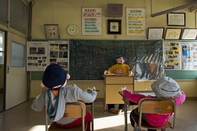 Scarecrows representing pupils and a teacher sit in a classroom in a closed down school in the village of Nagoro on Shikoku Island in southern Japan February 24, 2015. (Photo by Thomas Peter/Reuters)