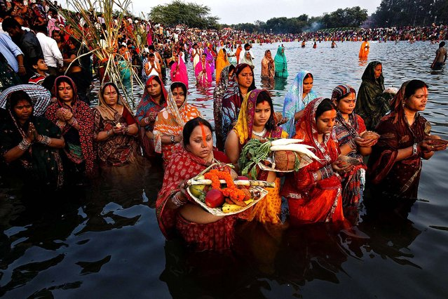 Hindu women carrying offerings stand in the waters of Sun Lake as they worship the Sun god Surya during the Hindu religious festival of Chatt Puja in the northern Indian city of Chandigarh, on November 8, 2013. Women fast for the whole day for the betterment of their family and the society during the festival. (Photo by Ajay Verma/Reuters)