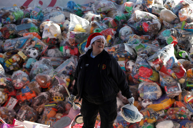 A volunteer smiles as she stands next to bags with toys during an annual gift-giving event organised by firefighters, who collect donated toys throughout the year and hand them out to needy children on Christmas eve, in Ciudad Juarez, Mexico, December 24, 2016. (Photo by Jose Luis Gonzalez/Reuters)