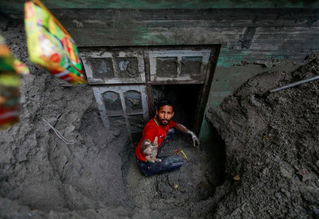 A man works to retrieve belongings from a house partially submerged in mud after the area was hit by flash floods along the bank of Melamchi River in Sindhupalchok, Nepal on June 20, 2021. (Photo by Navesh Chitrakar/Reuters)