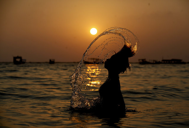 The sun sets as a girl enjoys water at Ngapali Beach, Tandwe township, western Myanmar, February 28, 2015. Ngapali is the most popular beach of Myanmar attracting tourists and also locals. (Photo by Lynn Bo Bo/EPA)