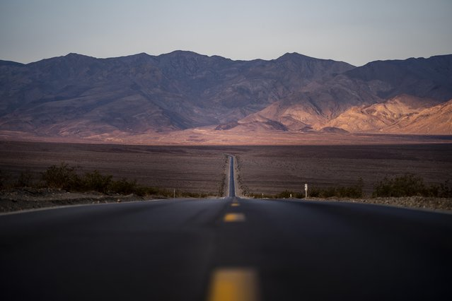 The sun rises onto the Panamint Mountain Range seen from Highway 190 during a weekend of extreme record breaking high temperatures reaching 135 degrees fahrenheit in Death Valley National Park, California Sunday July 11, 2021. (Photo by Melina Mara/The Washington Post)