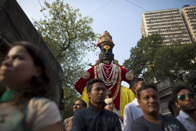 People stand in front of an idol of Hindu god Vitthal as they watch celebrations to mark the Gudi Padwa festival in Mumbai March 21, 2015. (Photo by Danish Siddiqui/Reuters)