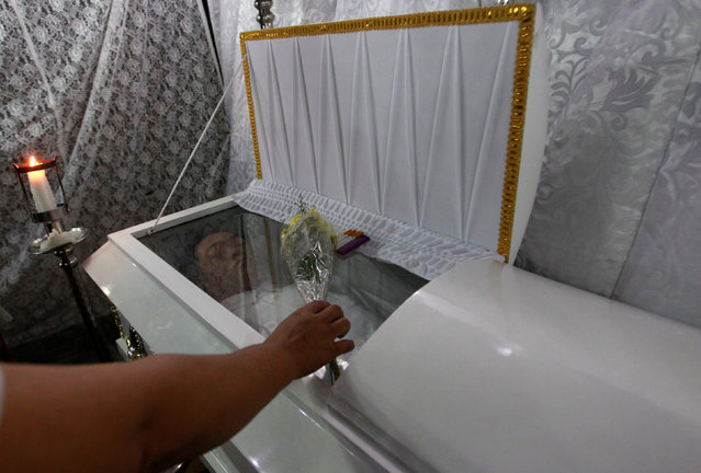 A relative of Ednel Santor, 22, who according to police was killed by unidentified gunmen at a drug den, places flowers at Ednel's coffin in Caloocan city, Metro Manila, Philippines December 30, 2016. (Photo by Czar Dancel/Reuters)