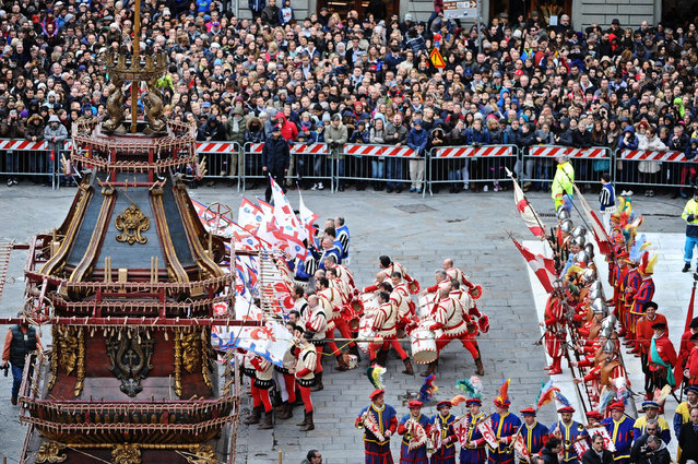 """Turists and residents gather in Duomo Square to watch the traditional """"Scoppio del Carro"""" (Explosion of the Cart) ceremony in Florence, Italy, April 5, 2015. Every year on Easter Sunday in Florence a rocket shaped like a dove, the Colombina, darts forth from the Duomo, setting on fire the big cart on the square which is laden with firecrackers and fireworks. (Photo by Maurizio Degli Innocenti/AP Photo/ANSA)"""