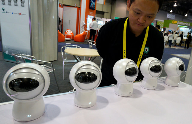 Rensong Liu looks over a display of Moorebot robot assistants at the Robotics Marketplace at CES in Las Vegas, U.S., January 5, 2017. (Photo by Rick Wilking/Reuters)