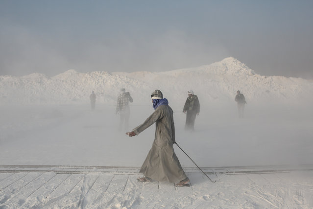 In this Wednesday, March 18, 2015 photo, limestone quarry workers walk through a cloud of dust spewed into the air by rotor blades of the stone-cutting machinery in the desert of Minya, southern Egypt. (Photo by Mosa'ab Elshamy/AP Photo)