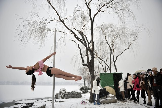 This picture taken on December 17, 2013 shows people watching a pole dancer (L) practise after it snowed in Tianjin during a promotional event by members of China's national pole dancing team and students of the sport. (Photo by AFP Photo)