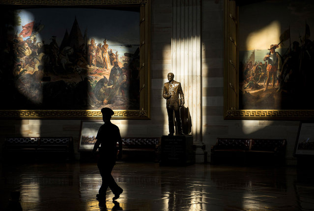 A US Capitol Police Officer walks past a statue of Gerald Ford, who was US president during the 1976 shutdown of the federal government, in the Rotunda while the building was closed to tours on Capitol Hill October 1, 2013 in Washington, DC. (Photo by Brendan Smialowski/AFP Photo)