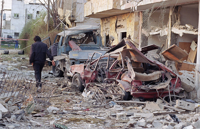 In this January 18, 1991 file photo, a person walks through the debris in Tel Aviv after eight Iraqi scud missiles were fired at Israel. Twenty five years after the first U.S. Marines swept across the border into Kuwait in the 1991 Gulf War, American forces find themselves battling the extremist Islamic State group, born out of al-Qaida, in the splintered territories of Iraq and Syria. In Israel, the memory of Iraqi Scud missile fire prompted the military to speed up a missile-defense program that included the development of its Iron Dome rocket-defense system with the help of the Americans. (Photo by John Gaps III/AP Photo)