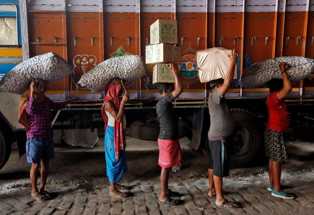 Labourers stand in a queue to load sacks of garlic and grocery items onto a supply truck at a wholesale market in Kolkata, India January 21, 2019. (Photo by Rupak De Chowdhuri/Reuters)