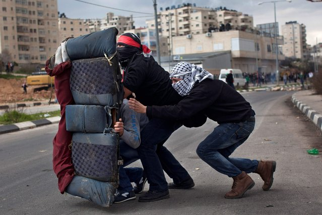 Masked Palestinians use a back car seat as a shield during a protest to support Palestinian prisoners, outside Ofer, an Israeli military prison near the West Bank city of Ramallah, Tuesday, February 19, 2013. (Photo by Bernat Armangue/AP Photo)