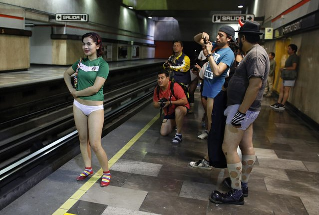 """A woman without pants is photographed by members of her team at an underground platform during the """"No Pants Subway Ride"""" in Mexico City January 12, 2014. (Photo by Tomas Bravo/Reuters)"""