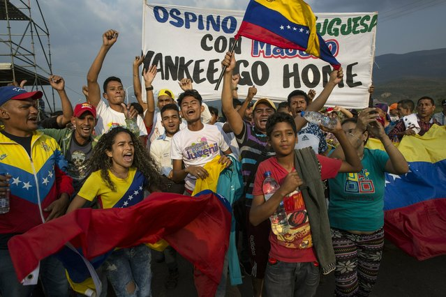 "Government supporters chant anti-U.S. slogans during the first day of the ""Hands off Venezuela"" three-day music festival at the Tienditas International Bridge, in Urena, Venezuela, Friday, February 22, 2019, on the border with Colombia. Venezuela's power struggle is set to convert into a battle of the bands Friday when musicians demanding Nicolas Maduro allow in humanitarian aid and those supporting the embattled leader's refusal sing in rival concerts being held at both sides of a border bridge where tons of donated food and medicine are being stored. (Photo by Rodrigo Abd/AP Photo)"