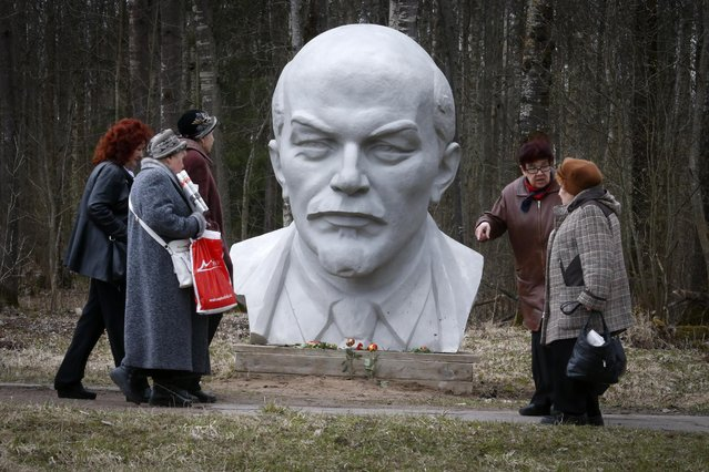 People walk past a statue of Soviet Union founder Vladimir Lenin during celebration of his 145th birthday at the Lenin Hut Museum at Razliv lake, outside St.Petersburg, Russia, Wednesday, April 22, 2015. (Photo by Dmitry Lovetsky/AP Photo)