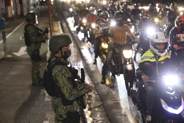 Police officers inspect motorcycle riders at a checkpoint during a stricter lockdown as a precaution against the spread of the coronavirus at the outskirts of Marikina City, Philippines on Friday, August 6, 2021. Thousands of people jammed coronavirus vaccination centers in the Philippine capital, defying social distancing restrictions, after false news spread that unvaccinated residents would be deprived of cash aid or barred from leaving home during a two-week lockdown that started Friday. (Photo by Basilio Sepe/AP Photo)