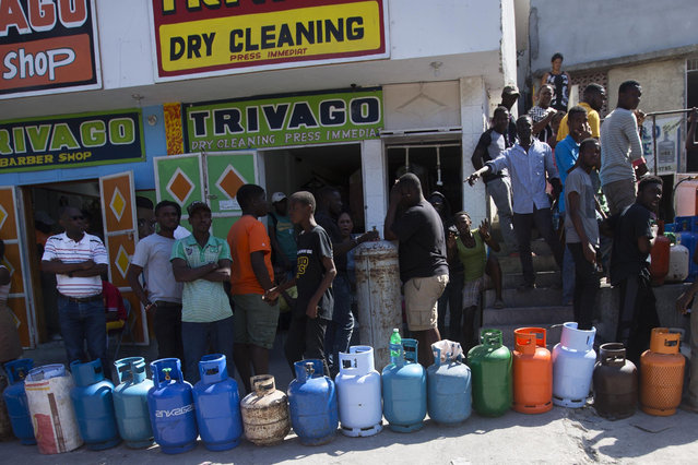 Residents line up to buy propane gas in Port-au-Prince, Haiti, Monday, February 18, 2019. Businesses and government offices slowly reopened across Haiti on Monday after more than a week of violent demonstrations over prices that have doubled for food, gas and other basic goods in recent weeks and allegations of government corruption. (Photo by Dieu Nalio Chery/AP Photo)