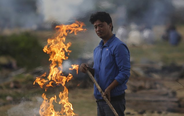 A man stands next to the burning pyre of a family member at a cremation ground after Saturday's earthquake in Bhaktapur, Nepal April 27, 2015. (Photo by Adnan Abidi/Reuters)
