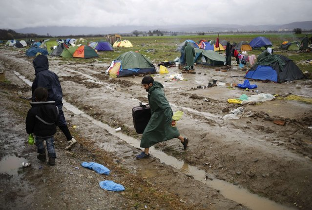 Migrants walk in a mud at a makeshift camp on the Greek-Macedonian border, near the village of Idomeni, Greece March 10, 2016. (Photo by Stoyan Nenov/Reuters)