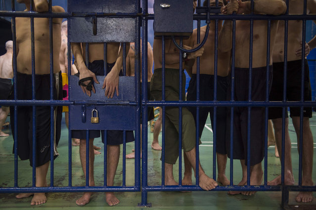 Foreign detainees stand behind bars at an immigration detention centre in Bangkok on January 21, 2019, during a visit organized by authorities for journalists. Rights groups have for years condemned Thailand, which is not a signatory to the UN's convention protecting refugees, for its hostility to asylum seekers – often trapping them on a carousel between detention and work in the black economy. (Photo by Romeo Gacad/AFP Photo)
