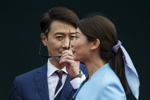Actor Leon Lai (L) takes off his glasses during a promotional event for Audemars Piguet Queen Elizabeth II Cup at Sha Tin Racecourse in Hong Kong April 26, 2015. (Photo by Tyrone Siu/Reuters)