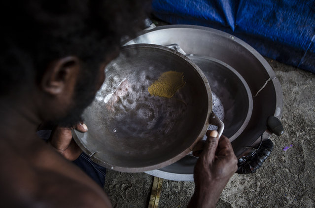Gold is seen on a pan as a illegal gold miner of Kamoro people, sift through sand at his temporary hut on February 4, 2017 in Timika, Papua Province, Indonesia. (Photo by Ulet Ifansasti/Getty Images)