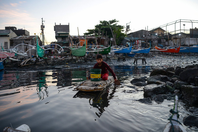 In this photo taken on March 10, 2019, 13-year-old Reymark Cavesirano paddles his borrowed makeshift craft made from styrofoam to fishing boats anchored at the mouth of Manila Bay off Navotas City in suburban Manila. Cavesirano, a grade five student, paddles to the anchored fishing boats and helps crew clean their nets, and in exchange collects leftover herring still tangled in the nets. After spending three hours in different boats he heads back to land and divides the catch up for his family's consumption with the rest sold to neighbours, earning around 100-150 pesos (2-3 USD) which he saves to support his school expenses. (Photo by Ted Aljibe/AFP Photo)