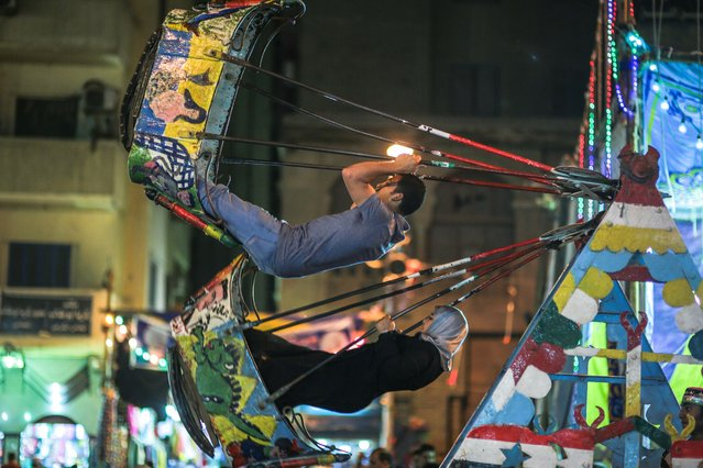 In this Tuesday, May 12, 2015 photo, people ride swing, as Muslims take part in a religious festival, or moulid, which commemorates the birth of the Muslim Prophet Muhammad's granddaughter, Sayyeda Zeinab, in a street outside the mosque and shrine named for her, in Cairo, Egypt. (Photo by Mosa'ab Elshamy/AP Photo)