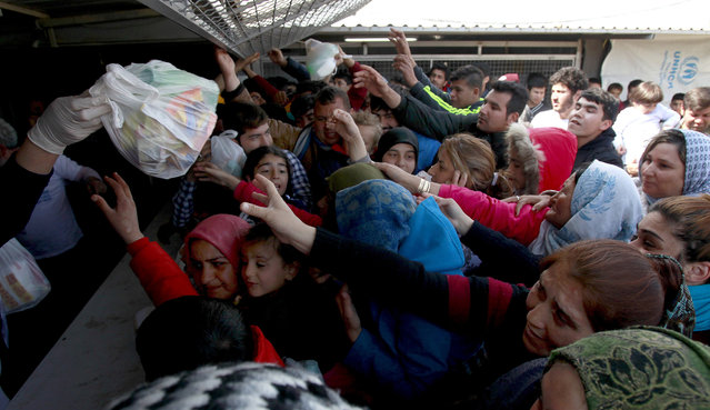 Refugees and migrants reach for food packages provided by humanitarian workers, at the transit center for refugees near northern Macedonian village of Tabanovce on the border with Serbia, Monday, March 28, 2016. (Photo by Boris Grdanoski/AP Photo)