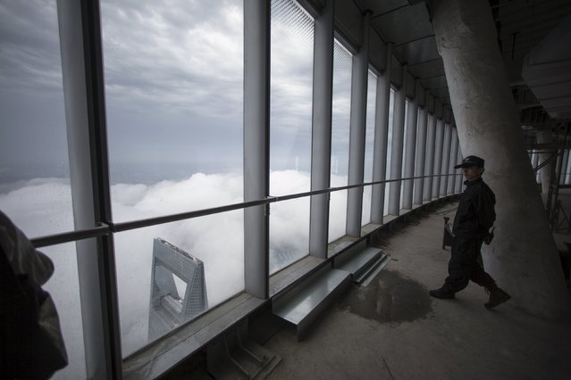 A security guard walks inside the top of the Shanghai Tower, during heavy rain at the financial district of Pudong in Shanghai May 15, 2015. The Shanghai Tower stands at approximately 632 metres (2,073 ft) and will be the tallest skyscraper in China and the second tallest in the world when it is completed in the summer of 2015. (Photo by Aly Song/Reuters)