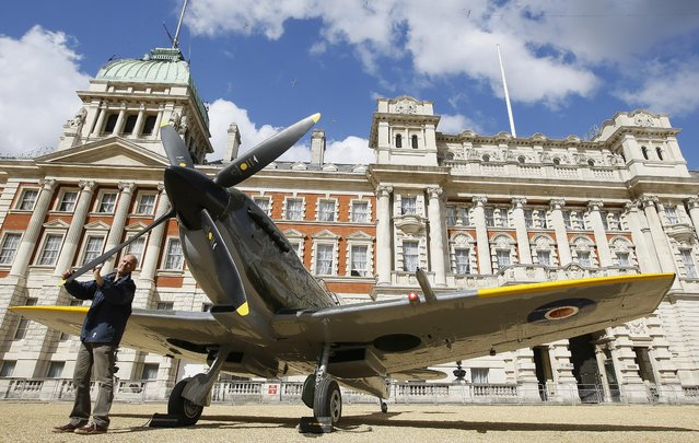 """Keith Lee, an RAF employee puts the finishing touches to a Second World War Spitfire Mk XVI, in Horse Guards Parade in London, Thursday, March 31, 2016. A Pop-Up RAF aircraft museum was on Horse Guards Parade to mark the centenary of the Royal Air Force.The planes were transported to the capital ahead of the 100th anniversary of the RAF. The display was organised by the RAF Museum to highlight the way the air force has """"shaped the modern world and touched the lives of millions"""". (Photo by Kirsty Wigglesworth/AP Photo)"""
